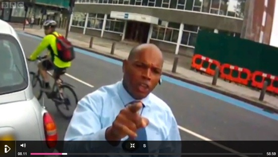 An angry motorist pointing their finger at a camera