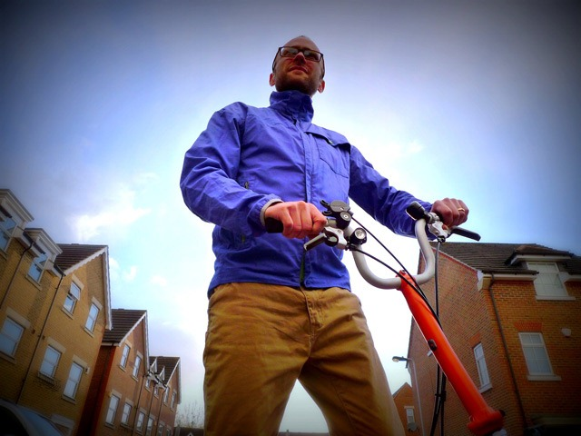 The blue Vulpine jacket is shown from a bottom angle with a folding bike in the frame